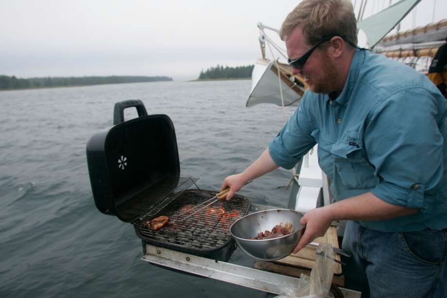 TRAVEL MAINE -- Capt. Troy Sullivan grills chicken and steak on a barbecue clamped to the side of the Grace Bailey, an 82-foot schooner that sails around Penobscot Bay, Maine.