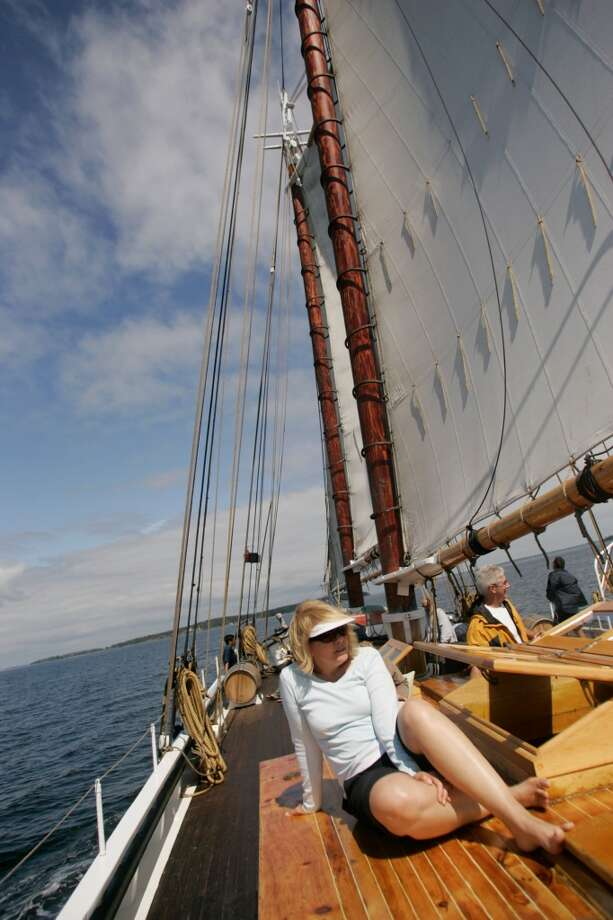 Passengers relax during a sailing day aboard the Grace Bailey, a two-masted schooner that makes 5-day voyages around Penobscot Bay, Maine.