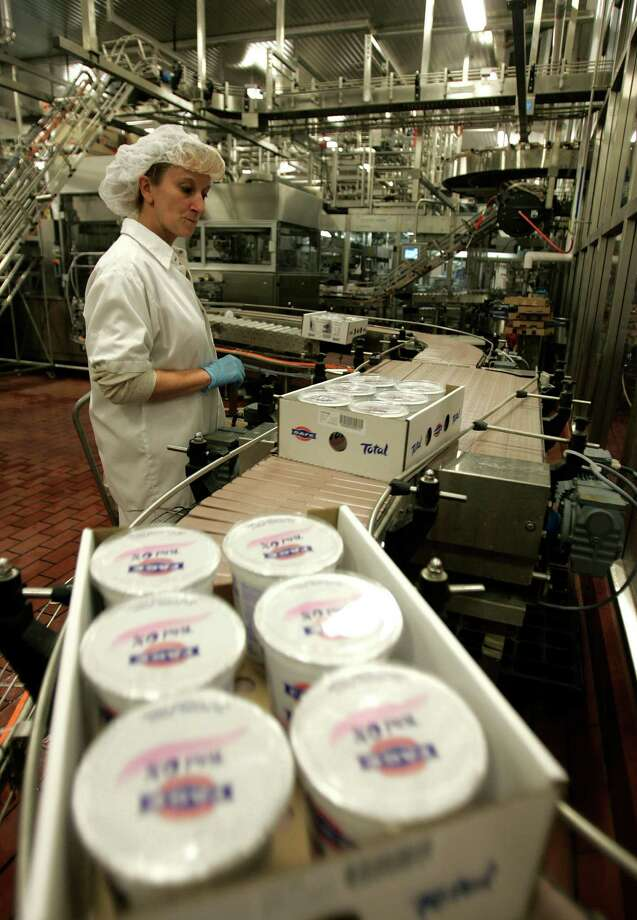 FILE - In this Dec. 10, 2008 file photo, a worker monitors the production line as cases of Fage yogurt are produced in Johnstown, N.Y.  Whey, a byproduct of Greek yogurt production, is collected at Gloversville-Johnstown wastewater plant west of Albany, N.Y., and mixed with anaerobic bacteria. The resulting methane gas becomes combustible fuel that generates nearly enough electricity to power the plant. (AP Photo/Mike Groll, File) Photo: Mike Groll