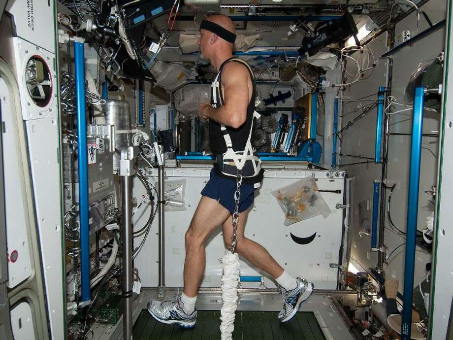 In the Harmony node of the Earth-orbiting International Space Station, European Space Agency astronaut Luca Parmitano exercises on the Combined Operational Load Bearing External Resistance Treadmill (COLBERT) on June 2, 2013.