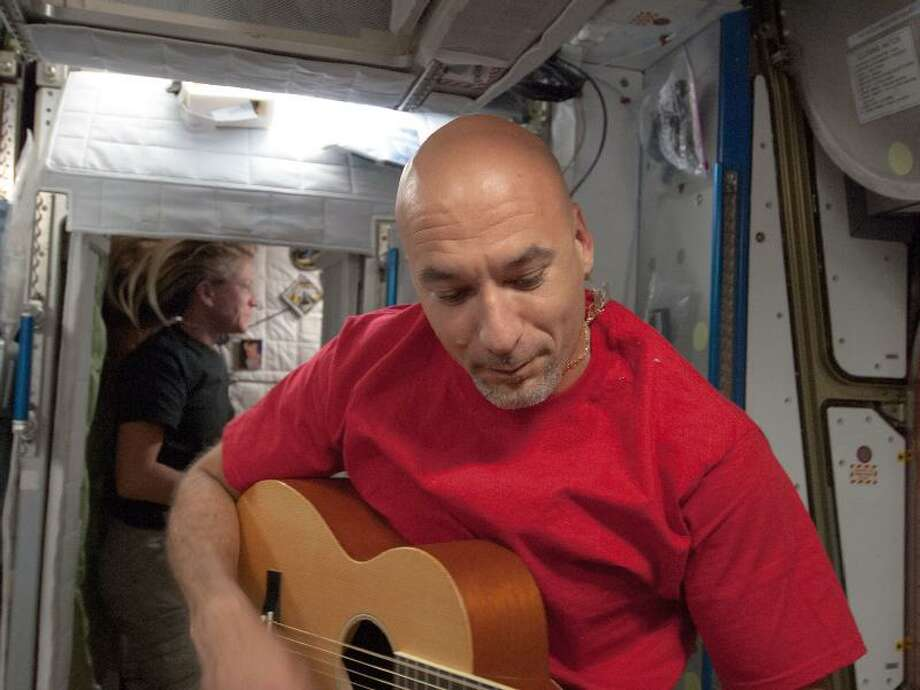 European Space Agency astronaut Luca Parmitano, Expedition 36 flight engineer, plays a guitar during some of his off-duty time aboard the International Space Station on May 31..
