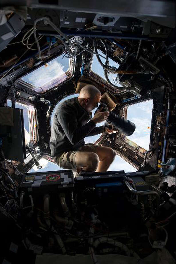 Inside the Cupola, NASA astronaut Chris Cassidy, an Expedition 36 flight engineer, eyeballs a point on Earth some 250 miles below him.