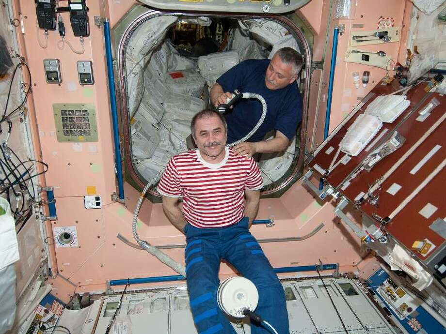 It's haircut day for Expedition 36 Commander Pavel Vinogradov, a cosmonaut with Russia's Federal Space Agency (Roscosmos), in the Unity node aboard the International Space Station. Doing the honors as his barber is Roscosmos cosmonaut Fyodor Yurchikhin, flight engineer for Expedition 36.