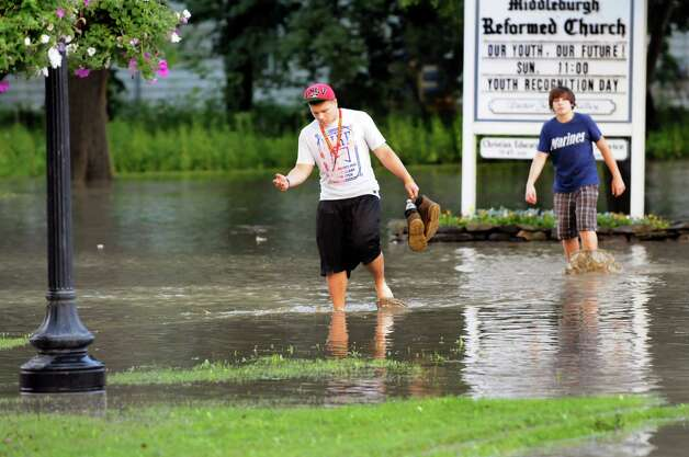 Armando DeLuca, 18, left, and his brother Dominic, 14, wade through flood waters on River Street on Friday, June 14, 2013, in Middleburgh, N.Y. The boys, whose home was unaffected, were seeing if other residents needed help. (Cindy Schultz / Times Union) Photo: Cindy Schultz