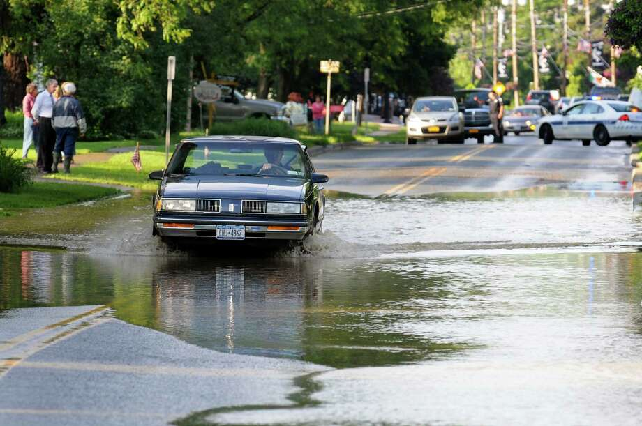 A car drives through flood waters on Main Street on Friday, June 14, 2013, in Schoharie, N.Y. (Cindy Schultz / Times Union) Photo: Cindy Schultz