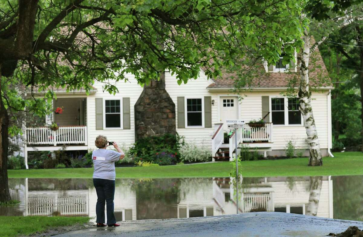 Resident Linda Godoy photographs a neighbor's home surrounded by flood waters on Friday, June 14, 2013, in Schoharie, N.Y. (Cindy Schultz / Times Union)