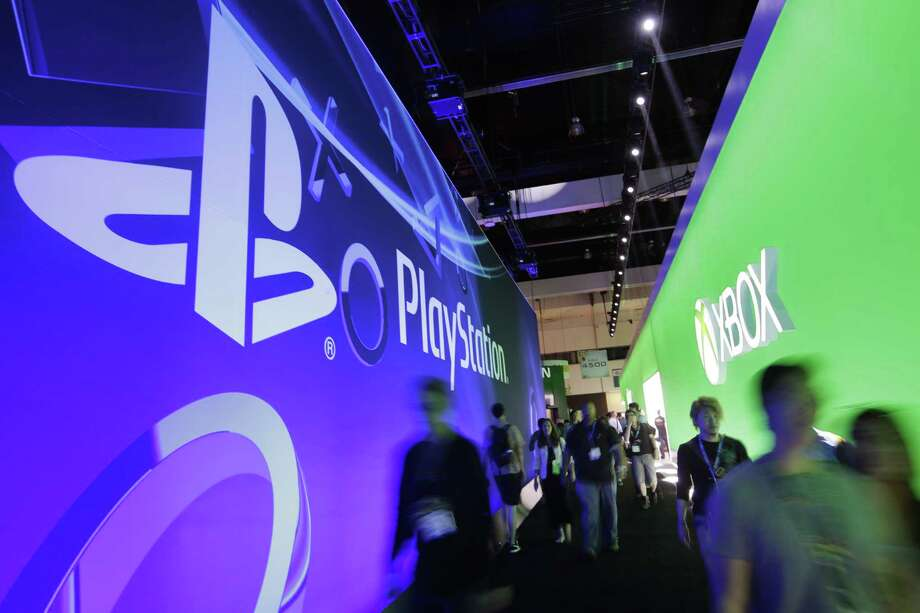 Show attendees walk down the aisle between the Sony and Microsoft booths Wednesday during the Electronic Entertainment Expo in Los Angeles. Photo: Associated Press
