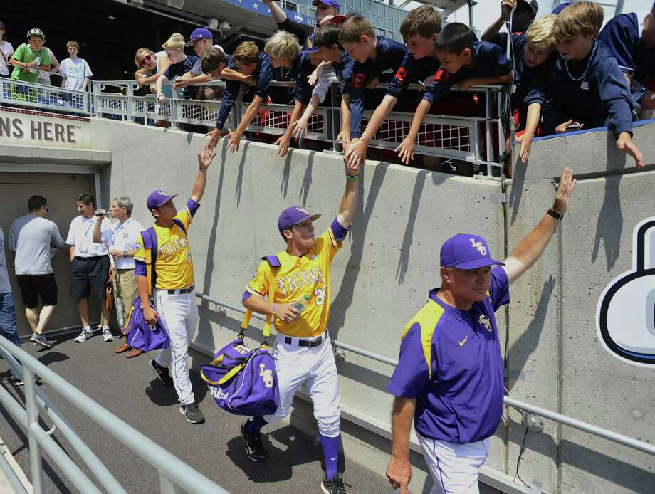 LSU coach Paul Mainieri (right) leads his players out for a practice Friday at TD Ameritrade Park. Though a No. 4 seed, the Tigers are the consensus top-ranked team in the major polls. Photo: Eric Francis / Associated Press