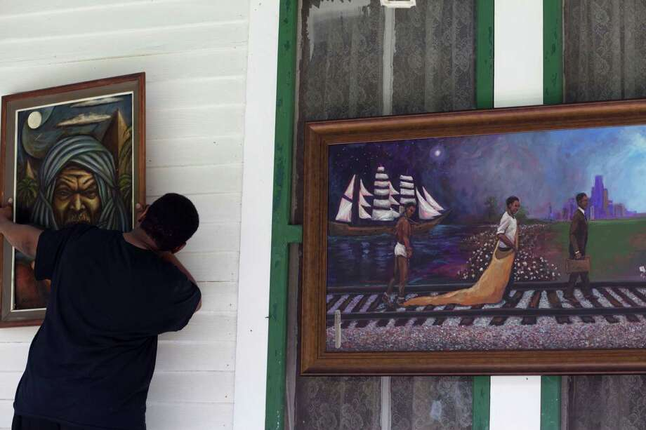 Sam Collins III hangs a painting of a Nubian by artist Earl Jones as he prepares for the 8th Annual Juneteenth Family Day in Hitchcock. Photo: Eric Kayne, For The Chronicle / ©2013 Eric Kayne