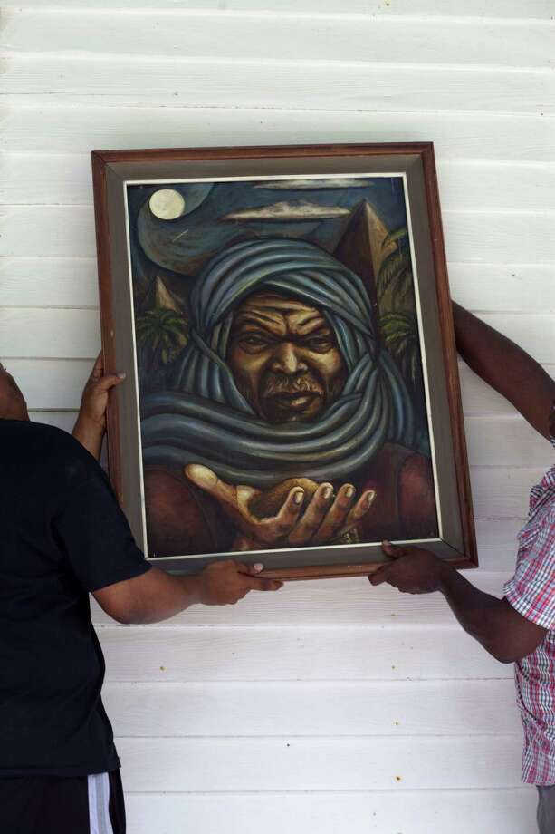 Sam Collins III, left, and Artist Earl Jones and hang a painting of a Nubian made by Jones as they prepare for the 8th Annual Juneteenth Family Day in Hitchcock. Photo: Eric Kayne, For The Chronicle / ©2013 Eric Kayne