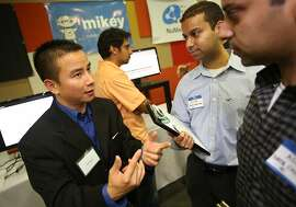 Co-founder and CEO of appfluence, an application that helps busy people prioritize their tasks, Hai Nguyen, left, explains his companies product to venture capitalists Alim Giga, center, and his brother Asif Giga at Startx Demo Day in Palo Alto, Calif. on Thursday, May 30, 2013. StartX is an non-profit that partners with Stanford students to facilitate start up businesses.