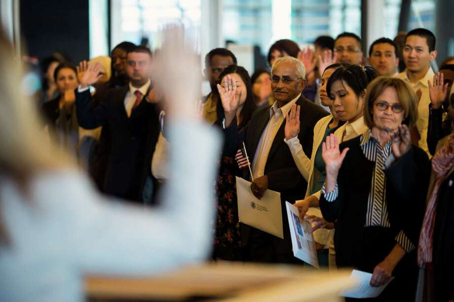 Fifty-five people swear in as U.S. citizens along with USCIS District Director Anne Corsano, left, during a naturalization ceremony put on by the Citizenship and Immigration Services, Seattle District 20, OneAmerica and the Seattle Office of Immigrant and Refugee Affairs on Friday, June 14, 2013, at Seattle City Hall in Seattle. The ceremony was part of a larger event celebrating Flag Day, which included local artists, face painting, crafts for kids and resources for new citizens. Photo: JORDAN STEAD, SEATTLEPI.COM / SEATTLEPI.COM
