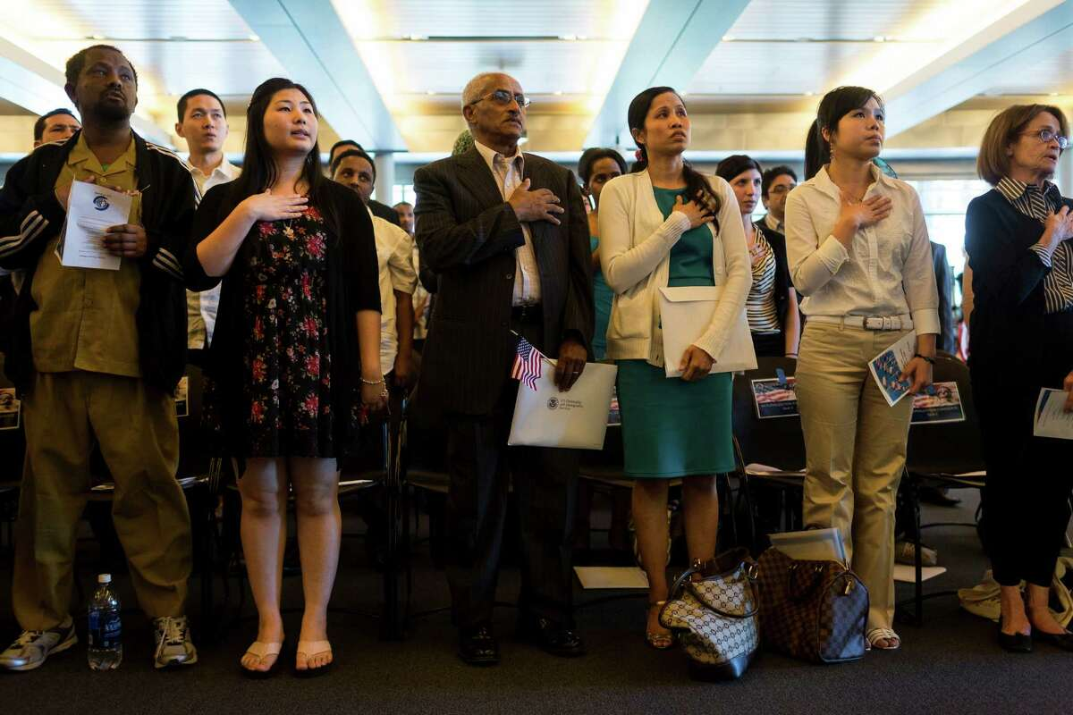 Fifty-five people stand during the National Anthem before swearing in as U.S. citizens during a naturalization ceremony put on by the Citizenship and Immigration Services, Seattle District 20, OneAmerica and the Seattle Office of Immigrant and Refugee Affairs on Friday, June 14, 2013, at Seattle City Hall in Seattle. The ceremony was part of a larger event celebrating Flag Day, which included local artists, face painting, crafts for kids and resources for new citizens.