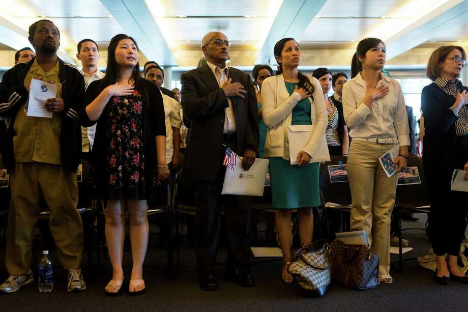 Fifty-five people stand during the National Anthem before swearing in as U.S. citizens during a naturalization ceremony put on by the Citizenship and Immigration Services, Seattle District 20, OneAmerica and the Seattle Office of Immigrant and Refugee Affairs on Friday, June 14, 2013, at Seattle City Hall in Seattle. The ceremony was part of a larger event celebrating Flag Day, which included local artists, face painting, crafts for kids and resources for new citizens. Photo: JORDAN STEAD, SEATTLEPI.COM / SEATTLEPI.COM