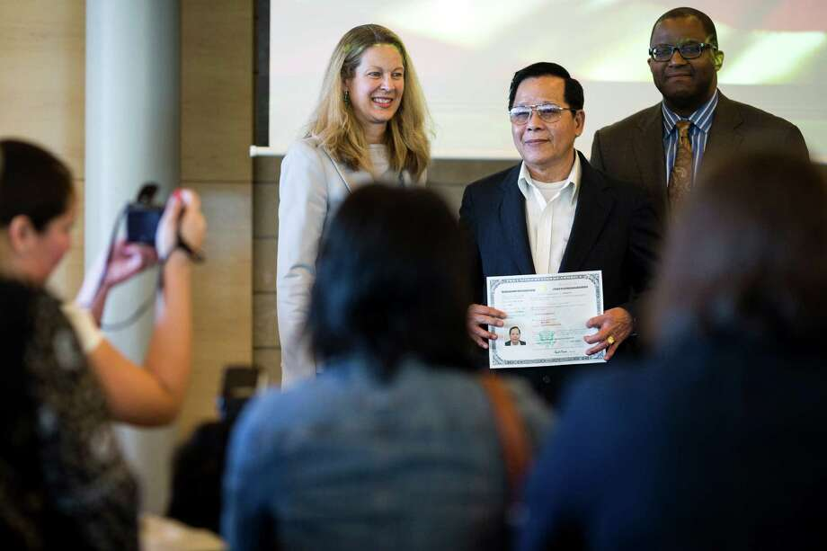 People accept their certificates after being sworn in as U.S. citizens during a naturalization ceremony put on by the Citizenship and Immigration Services, Seattle District 20, OneAmerica and the Seattle Office of Immigrant and Refugee Affairs on Friday, June 14, 2013, at Seattle City Hall in Seattle. The ceremony was part of a larger event celebrating Flag Day, which included local artists, face painting, crafts for kids and resources for new citizens. Photo: JORDAN STEAD, SEATTLEPI.COM / SEATTLEPI.COM