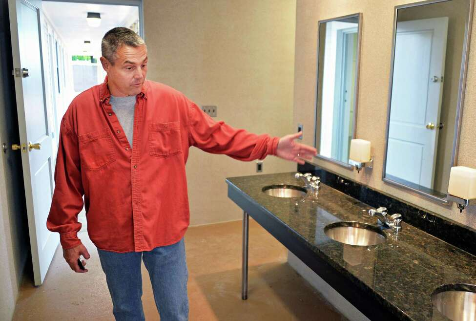 NYRA facilities manager for Saratoga, Peter Goulet in the new locker room-style bathrooms in the the first fully-renovated new dormitory for backstretch workers at Saratoga Race Course in Saratoga Springs, NY, Friday June 14, 2013. (John Carl D'Annibale / Times Union)