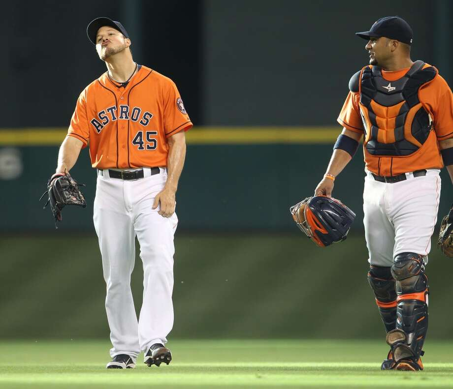 Astros starting pitcher Erik Bedard (45) walks out from the bullpen with catcher Carlos Corporan (22).