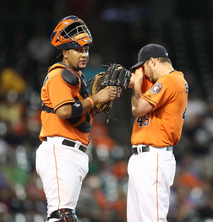 Astros catcher Carlos Corporan (22) chats with starting pitcher Erik Bedard (45) on the mound.