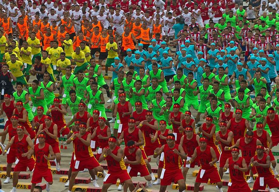 Inmates attend a group work-out at the Lurigancho prison on the outskirts of Lima, Peru, Friday, June 14, 2013. Inmates are attempting to break the Guinness World Record for the largest group of prisoners working out at the same time. (AP Photo/Martin Mejia) Photo: Martin Mejia, Associated Press