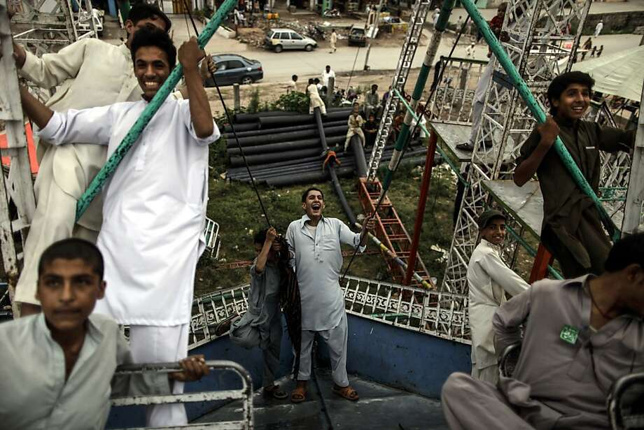 Pakistani youths enjoy a ride at a makeshift entertainment park set up outside a shrine in Rawalpindi, Pakistan, Friday, June 14, 2013. (AP Photo/Muhammed Muheisen) Photo: Muhammed Muheisen, Associated Press