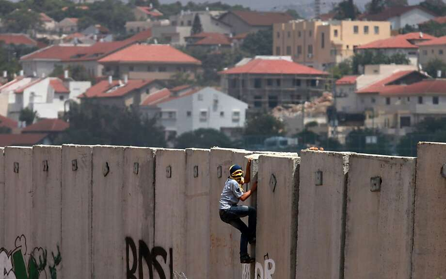 A Palestinian protester climbs Israel's controversial separation barrier during clashes with Israeli security forces following a demonstration against Israeli settlements and its separation wall, in the West Bank village of Nilin near the Jewish settlement of Hashmonaim (background), on June 14, 2013. AFP PHOTO/ ABBAS MOMANIABBAS MOMANI/AFP/Getty Images Photo: Abbas Momani, AFP/Getty Images