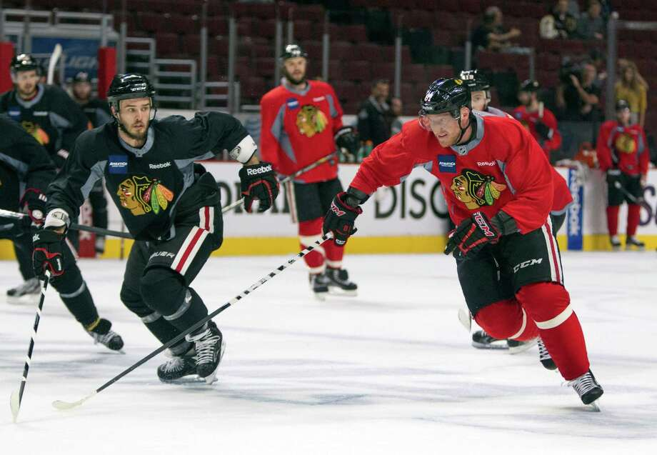 Chicago Blackhawks left wing Brandon Saad, right, skates past defenseman Niklas Hjalmarsson to get the puck during NHL hockey practice Friday, June 14, 2013, in Chicago. The Blackhawks lead the Boston Bruins 1-0 in the best-of-seven games Stanley Cup final series. Game 2 is scheduled for Saturday in Chicago.  (AP Photo/Scott Eisen) Photo: Scott Eisen