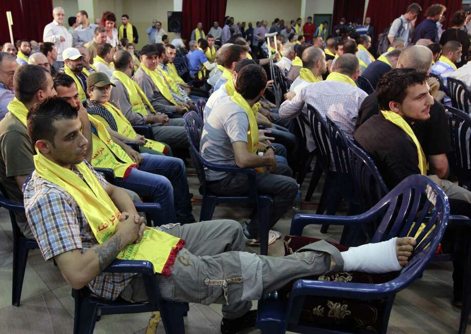 """An injured Hezbollah fighter who was wounded in Syria listens to a speech by Hezbollah leader Sheik Hassan Nasrallah via video during a rally to mark """"wounded resistants day"""" in Beirut. Photo: Bilal Hussein / Associated Press"""