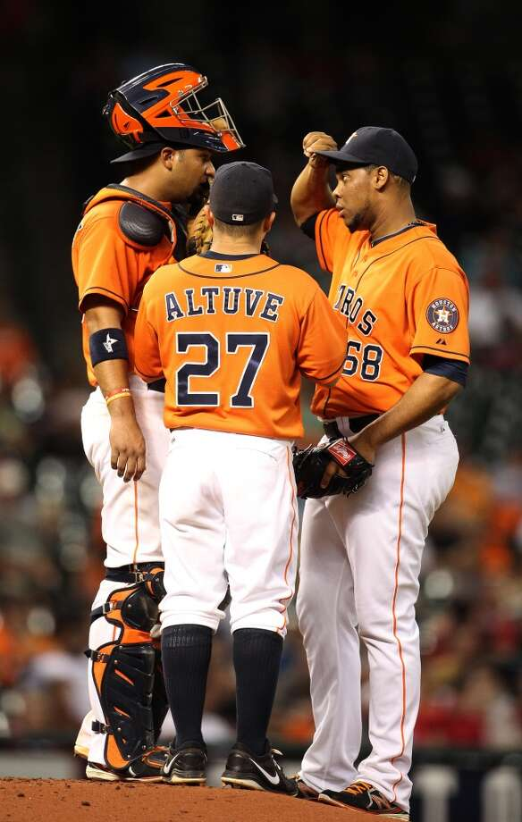 Astros relief pitcher Jose Cisnero  gets a visit on the mound from catcher Carlos Corporan and second baseman Jose Altuve.