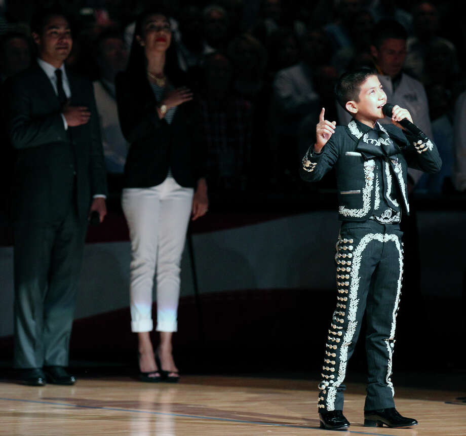 Sebastian De La Cruz sings the national anthem before the start of Game 4 of the NBA Finals at the AT&T Center on Thursday, June 13, 2013. Behind him are San Antonio's mayor Julian Castro and his wife. (Kin Man Hui/San Antonio Express-News) Photo: San Antonio Express-News / ©2013 San Antonio Express-News
