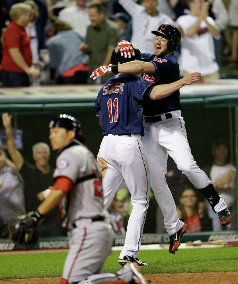 Ryan Raburn, right, celebrates with Drew Stubbs after Stubbs scored in the bottom of the ninth inning to send the Indians past the Nationals. Photo: Tony Dejak, STF / AP