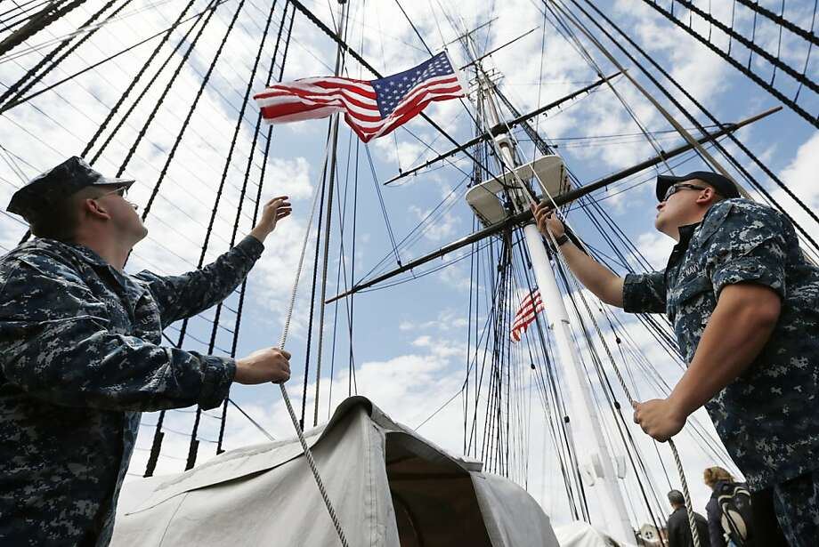 Navy airman Nathan McCutcheon, right, of Burton, Ala., and PS1 James Choyce, of Perkiomenville, Penn., lower a flag aboard the U.S.S. Constitution in Boston, Friday, June 14, 2013. The Constitution is the oldest commissioned warship in the U.S. Navy. (AP Photo/Michael Dwyer) Photo: Michael Dwyer, Associated Press