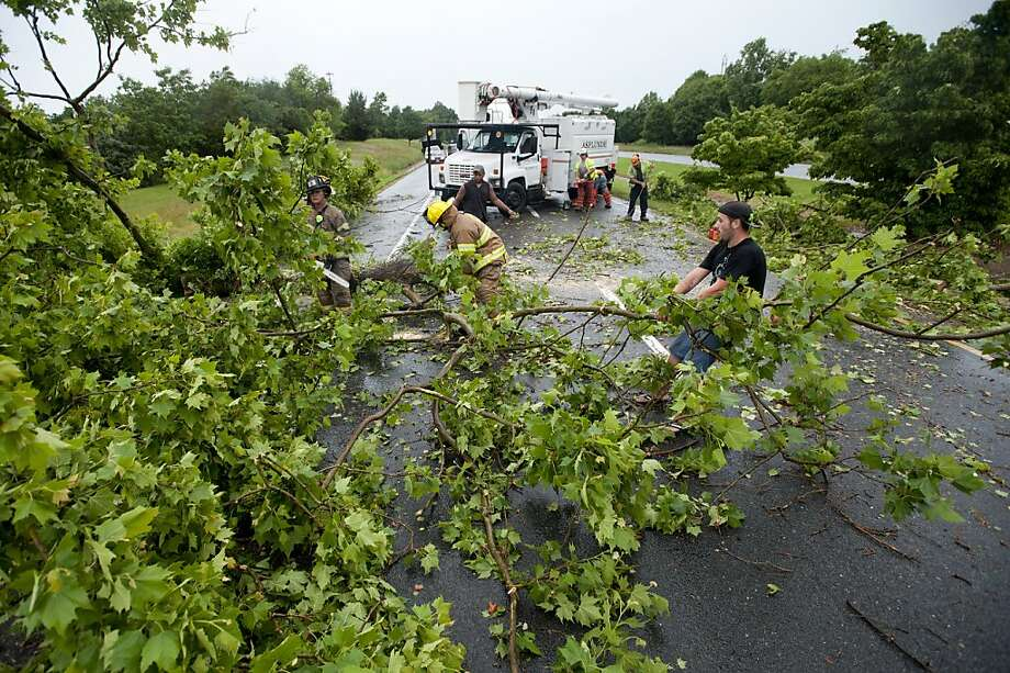Passing motorist Charles Jenkins, right, helps Lynchburg firefighters move branches of a tree that was blown over during the storm, blocking the southbound lanes of U.S. 501 through Lynchburg, Va. Thursday, June 13, 2013. About 140,000 homes and businesses remain without power in Virginia after a powerful storm pummeled the state. (AP Photo/The News & Advance, Parker Michels-Boyce) Photo: Parker Michels-boyce, Associated Press