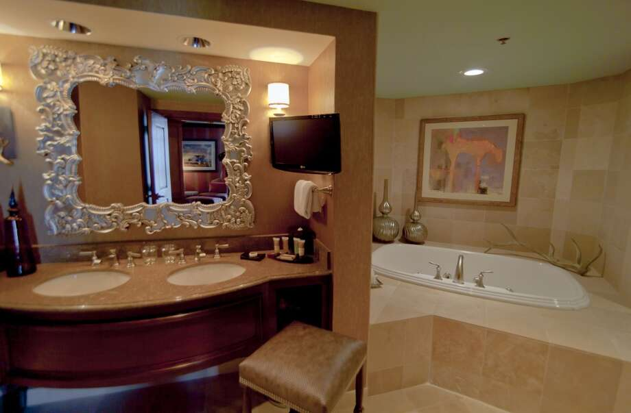 A big bold mirror and tasteful furnishings in the bathroom continue the Texas-style elegance in Grapevine's Grand Presidential Suite at the Gaylord Texan.