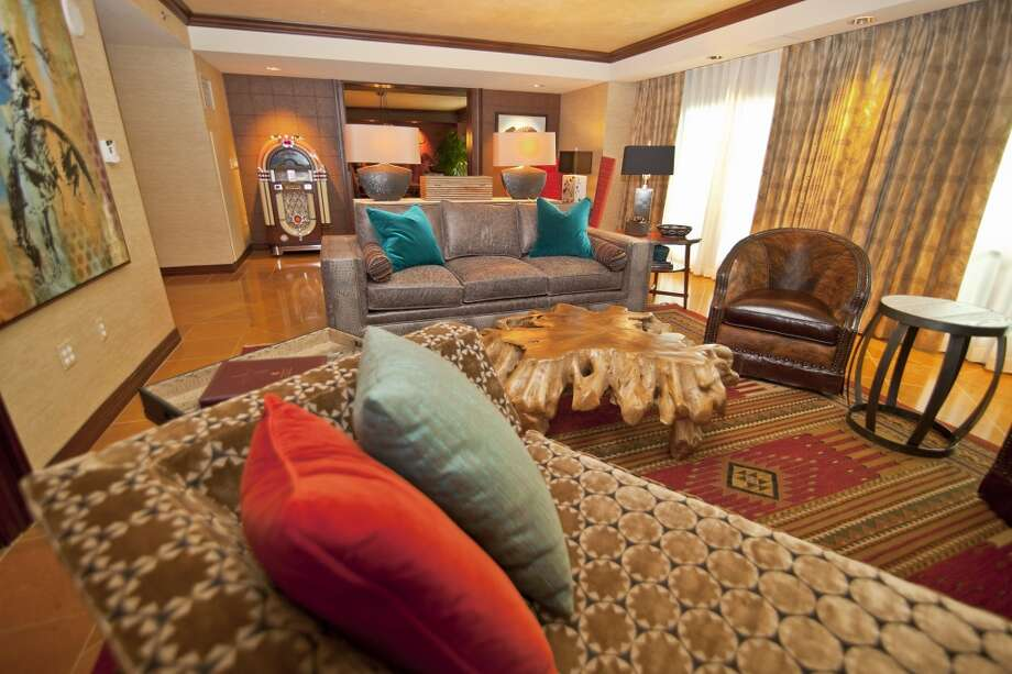 Pops of turquoise and orange surround the statement piece in this room -- a polished big tree-trunk coffee table in the Grapevine Grand Presidential Suite living room. Pull back the curtains for a view of fireworks over Lake Grapevine every Friday night in the summer.