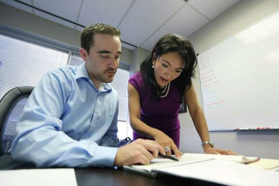 Justin Junkel and Nina Vaca look over a report during a recent meeting at her offices in Dallas. Vaca expects to hire more than 50 people for her firm, Pinnacle Technical Resources, by the end of 2013 as demand soars for the high-tech temporary workers it places.