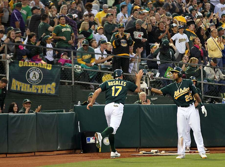 Adam Rosales is greeted by Chris Young after scoring on Eric Sogard's fifth-inning double. Photo: Lance Iversen, The Chronicle