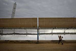 Laborers walk past a parabolic trough at the Godawari solar-thermal power plant, operated by Godawari Green Energy Ltd., near Nokh, Rajasthan, India, on Monday, June 10, 2013. Godawari Power & Ispat Ltd. started Asia's biggest solar-thermal plant as India limps toward clean-energy targets with prices almost half the global average. Photographer: Kuni Takahashi/Bloomberg