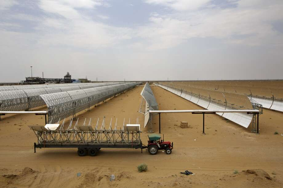 A tractor transporting panel components drives pasts parabolic troughs at the Godawari solar-thermal power plant, operated by Godawari Green Energy Ltd., near Nokh, Rajasthan, India, on Monday, June 10, 2013. Godawari Power & Ispat Ltd. started Asia's biggest solar-thermal plant as India limps toward clean-energy targets with prices almost half the global average. Photographer: Kuni Takahashi/Bloomberg Photo: Bloomberg
