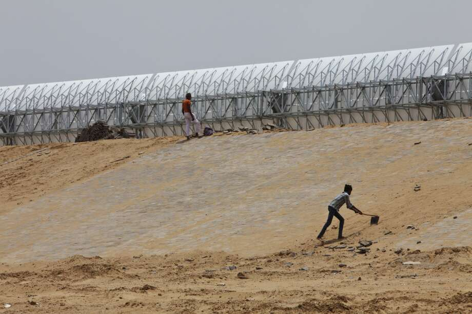 Laborers work on the banks of an unfinished second reservoir behind a parabolic trough at the Godawari solar-thermal power plant, operated by Godawari Green Energy Ltd., near Nokh, Rajasthan, India, on Monday, June 10, 2013. Godawari Power & Ispat Ltd. started Asia's biggest solar-thermal plant as India limps toward clean-energy targets with prices almost half the global average. Photographer: Kuni Takahashi/Bloomberg Photo: Bloomberg