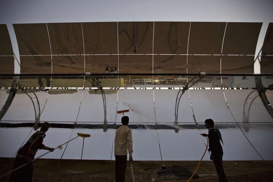 Workers clean the reflector panels of a parabolic trough at the Godawari solar-thermal power plant, operated by Godawari Green Energy Ltd., near Nokh, Rajasthan, India, on Sunday, June 9, 2013. Godawari Power & Ispat Ltd. started Asia's biggest solar-thermal plant as India limps toward clean-energy targets with prices almost half the global average. Photographer: Kuni Takahashi/Bloomberg Photo: Bloomberg