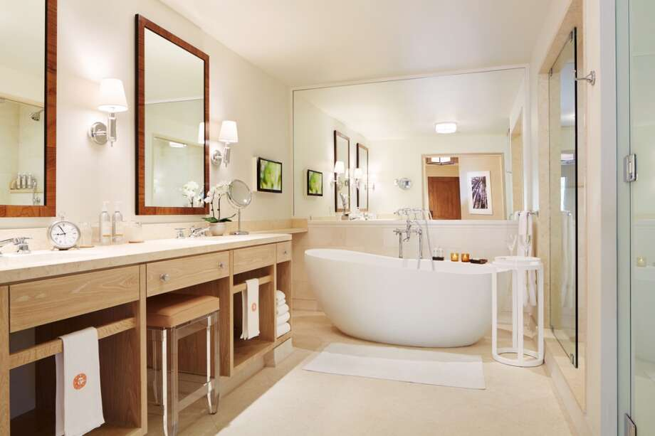 The bathrooms have a spa-like feel with slab stone, seated vanities, skylit showers and a sculptural tub.