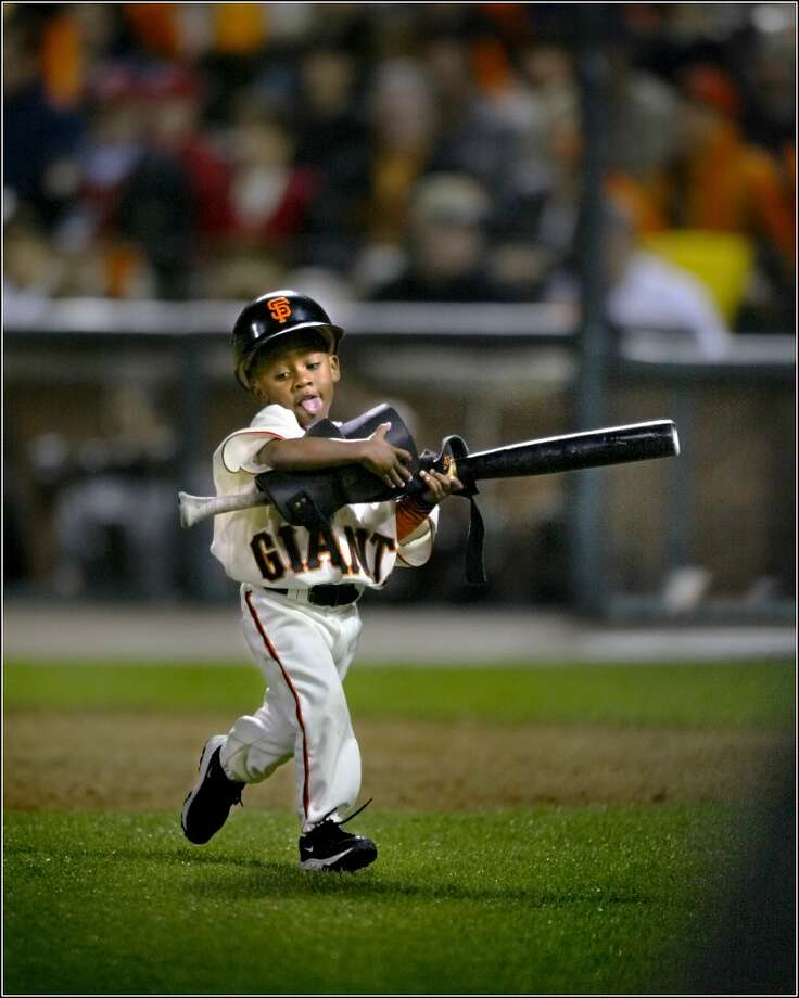 Darren, 3, son of manager Dusty Baker, runs off the field after retrieving the bat and elbow guard of Barry Bonds during Game 4 of the NLCS at Pac Bell Park in 2002.