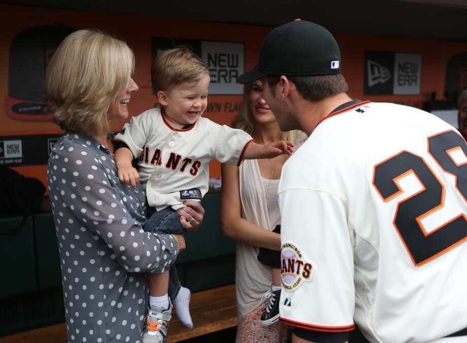 Buster Posey talks with his wife Kristin and mom Traci, who is holding his son Lee Dempsey Posey, before a ceremony honoring him as the 2012 National League MVP.