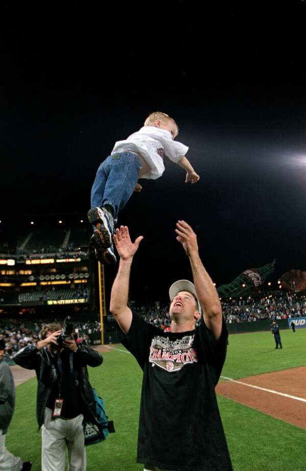 J.T. Snow tosses his son in celebration after the game against the Arizona Diamondbacks at Pac Bell Park in 2000.