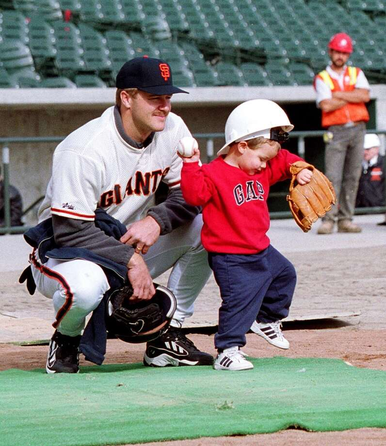 San Francisco Giants second baseman Jeff Kent watches his son, Hunter, 2, throw the ball, 21 January 2000, in San Francisco.