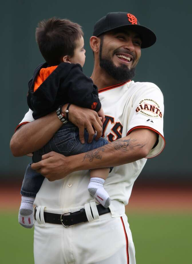 Sergio Romo holds his son Rex during a family softball game on the field before the game against the Los Angeles Dodgers at AT&T Park on Saturday, July 28, 2012.