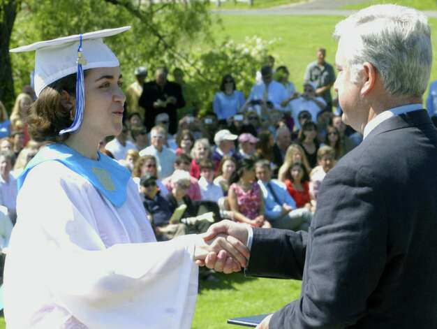 McKayla Sturges proudly receives a handshake and then her diploma from Region 12 Board of Education chairman James Hirschfield Saturday during Shepaug Valley High School's commen