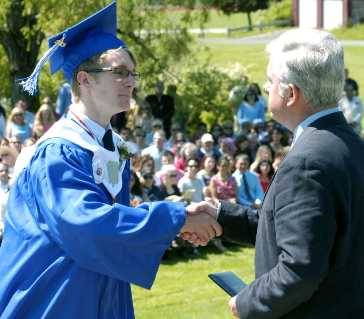 Ellery Rourke offers Region 12 Board of Education Chairman James Hirschfield an appreciative handshake as he receives his diploma Saturday during Shepaug Valley High School's commencement ceremony for the Class of 2013. June 16, 2013
