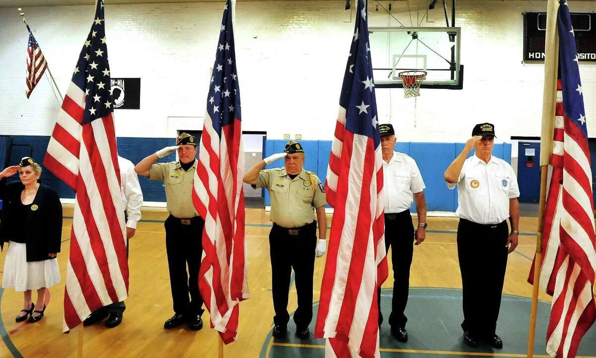 The Danbury Elks Lodge #120 holds Flag Day Service at the War Memorial in Danbury, Conn. Saturday, June 15, 2013. Saluting the flags of the United States of America from left are Patricia Terry, Allen Keeler, Luis Rosa, Ken Post and Brendan Sniffen.