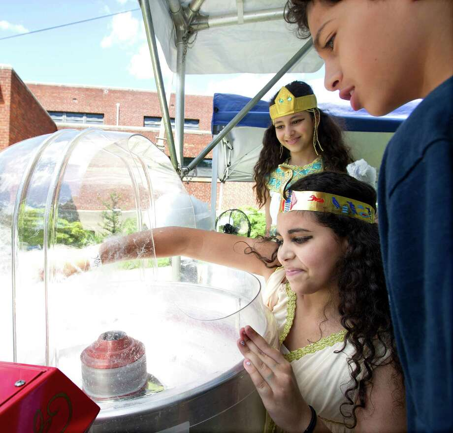 "From back to front, Isabella Sorial, 12, Michelle Awad, 12, and Daniel Sorial, 10, make cotton candy during ""A Taste of Egypt"" at St. Peter and St. Andrew Coptic Orthodox Church in Stamford, Conn., on Saturday, June 15, 2013. Photo: Lindsay Perry / Stamford Advocate"